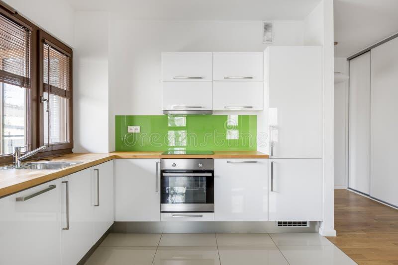 Glättat vitt kök med träfönstret royaltyfria bilder
