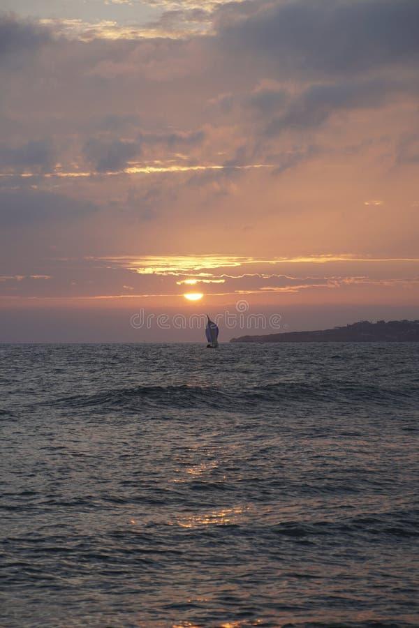 Glättung der Sonne über dem Ozean Yachtsegeln auf den Horizontstrahlen des Sonnenlichts Leuchtorangesonnenuntergang stockfoto