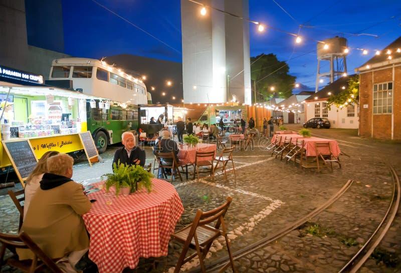 Glättung des Abendessens Restaurant am im Freien auf Kopfsteinstraße mit Tabellen und einigen Schnellimbiss-LKWs für Kunden lizenzfreie stockbilder
