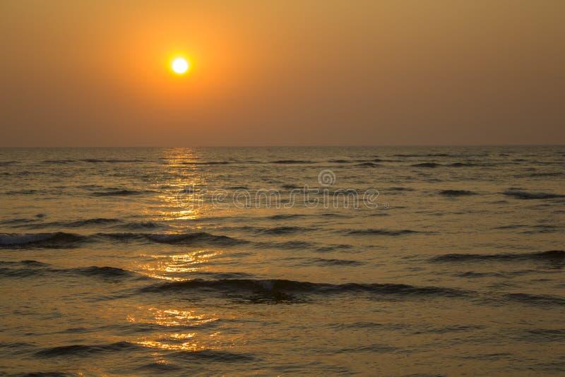 Glättung von Ozean mit einem Sonnenweg und von Wellen vor dem hintergrund des dunklen gelben Sonnenunterganghimmels stockbilder