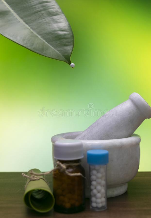 Glóbulo homeopático en la extremidad de una hoja y un mortero, una botella homeopática de la medicina de las píldoras con una hoj imagen de archivo