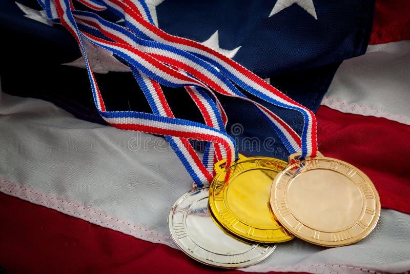 Glória e triunfo olímpicos no conceito da competição de esportes com três medalhas ouro, prata e bronze na bandeira dos EUA, repr imagens de stock
