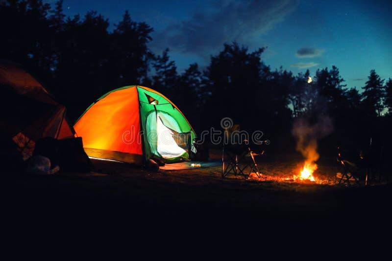 Glödande campa tält nära brasa i vildmark arkivfoto