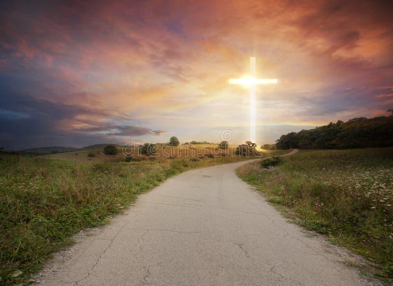 Glödande kors och väg arkivfoto