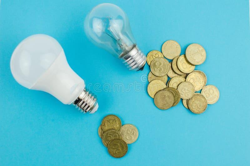 glödande lampa och energi - besparing på en blå bakgrund arkivbild