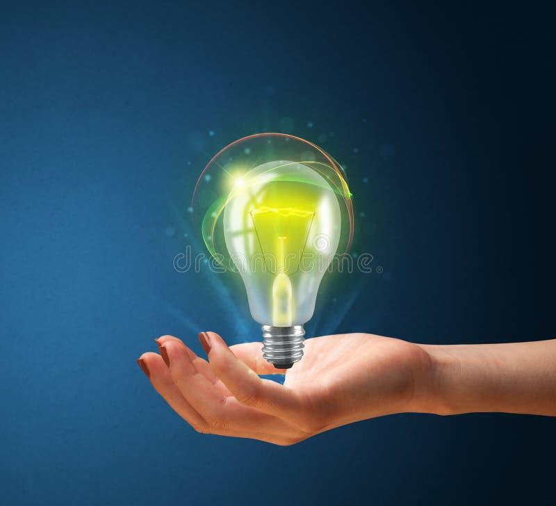 Glödande lightbulb i handen av en kvinna fotografering för bildbyråer