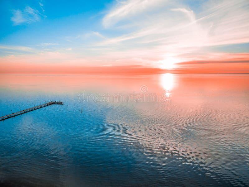 Glödande livlig röd solnedgång över havet royaltyfri bild