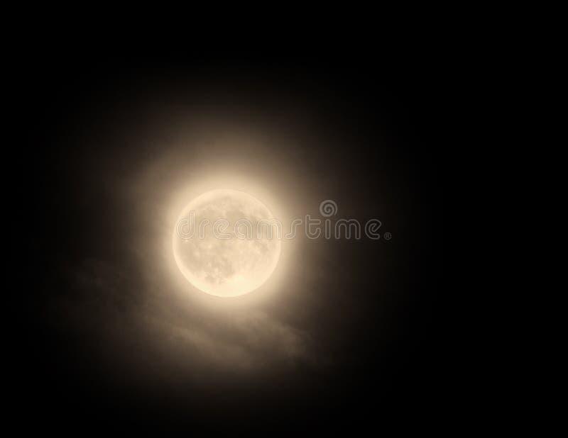 Glödande orange november fullmåne med ljust suddigt vid moln arkivfoton