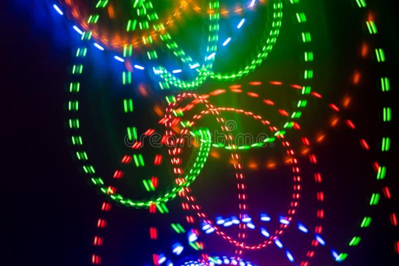 Glödande slaglängder för rundat intermittent färgrikt neon på svart bakgrund som tapeten arkivfoton