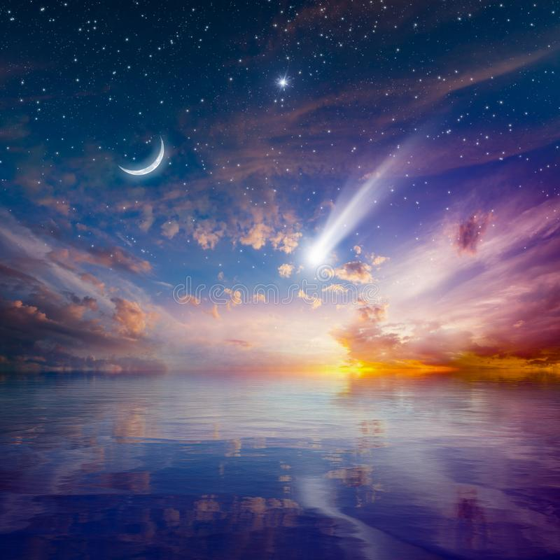Glödande solnedgång med den fallande komet, den stigande växande månen och stjärnan arkivbild