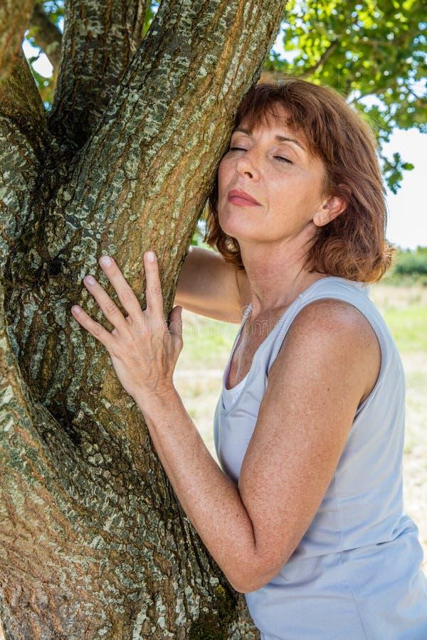 Glödande 50-talkvinna som trycker på ett träd i harmoni med naturen arkivfoton