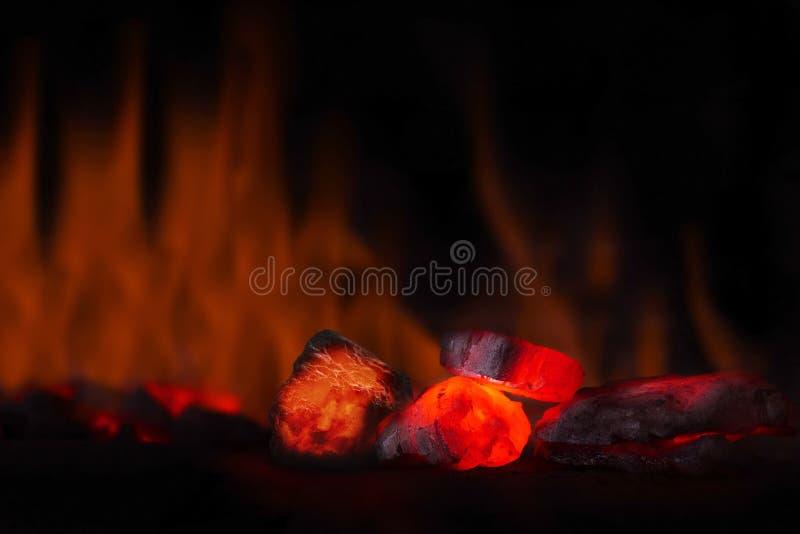 Glödhet kolklump i fokus på mörk bakgrund med flammor Bakgrund av rå kol med mjukt fokusuteslutande med färg och vikarier arkivfoto