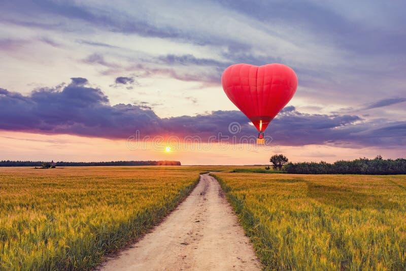 Glödhet luftballong i formen av en hjärta ovanför fältet royaltyfria bilder
