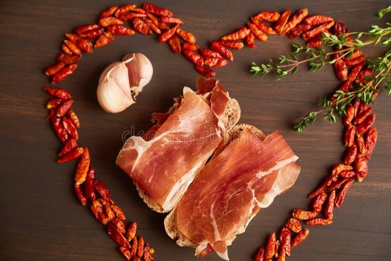 Glödhet peppar fodras i form av hjärta En filial av timjan, en kryddnejlika av vitlök Smörgåsar som göras från hand-gjort rågbröd arkivbild