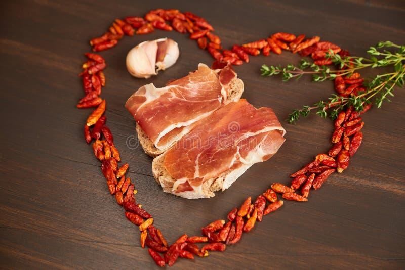 Glödhet peppar fodras i form av hjärta En filial av timjan, en kryddnejlika av vitlök Smörgåsar som göras från hand-gjort rågbröd arkivbilder