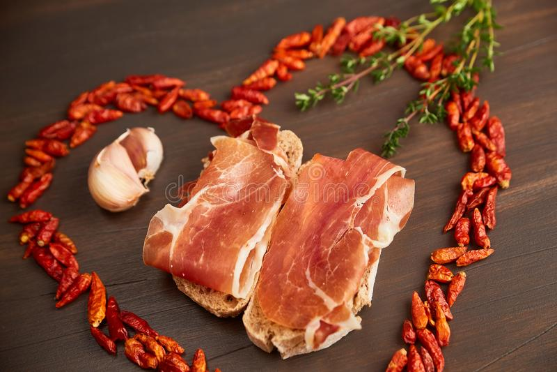 Glödhet peppar fodras i form av hjärta En filial av timjan, en kryddnejlika av vitlök Smörgåsar som göras från hand-gjort rågbröd royaltyfri fotografi