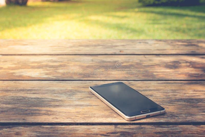 Glöm och förlora begreppet: Det svarta smartphonestället på trätabellen på offentligt parkerar royaltyfria bilder