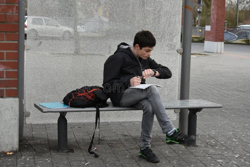 Glömd skolaläxa, pojke kontrollerar tiden till bussen ska ankomma fotografering för bildbyråer