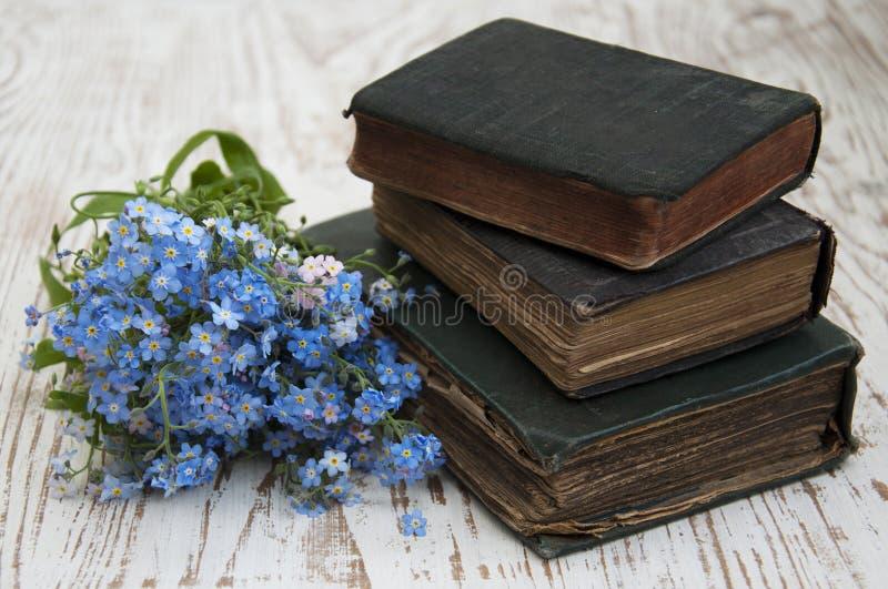 Glömma-mig-nots blommor och gamla böcker arkivbilder
