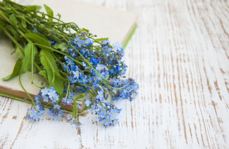 Glömma-mig-nots blommor och gammal bok arkivfoto