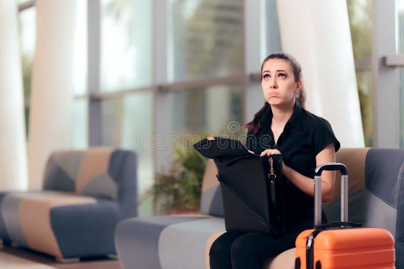 Glömsk flicka som kontrollerar hennes påse i en flygplats arkivbilder