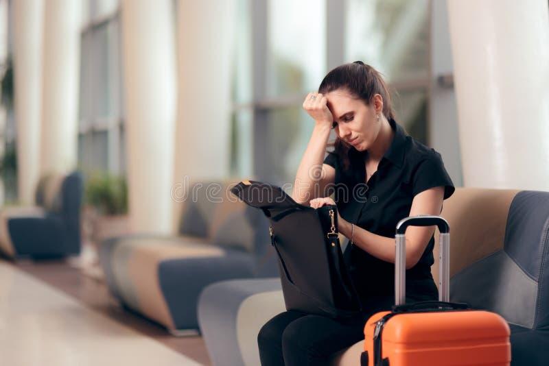 Glömsk flicka som kontrollerar hennes påse i en flygplats arkivfoto