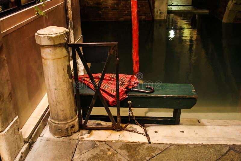 Glömt rött paraply på en grön bänk i Venedig arkivfoto