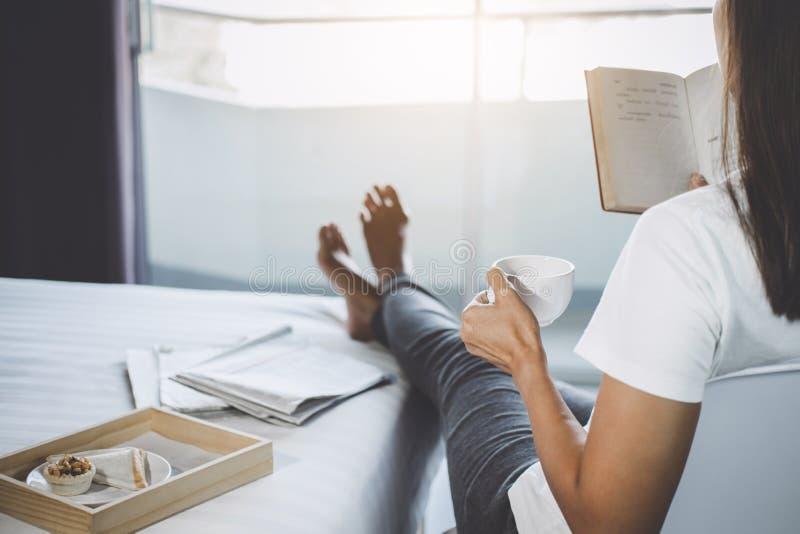 Glück der jungen Frau auf Schlafzimmer, wenn Lesebücher und n genossen werden stockfotografie
