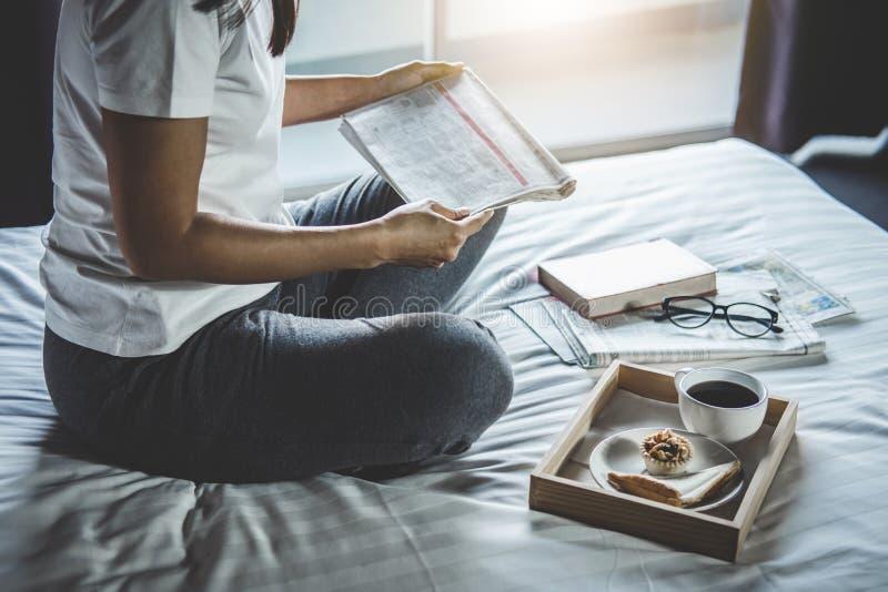 Glück der jungen Frau auf Schlafzimmer, wenn Lesebücher und -zeitung im Feiertag mit Morgenkaffee, -entspannung und -erholung gen lizenzfreies stockbild