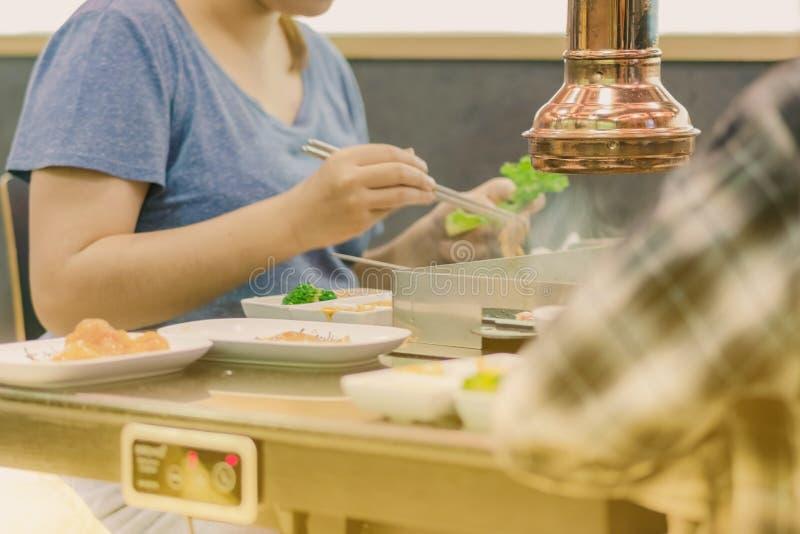 Glück Enjoy koreanische traditionelle berühmte Nahrung BBQ mit Familie in einem koreanischen Restaurant essend lizenzfreie stockfotografie