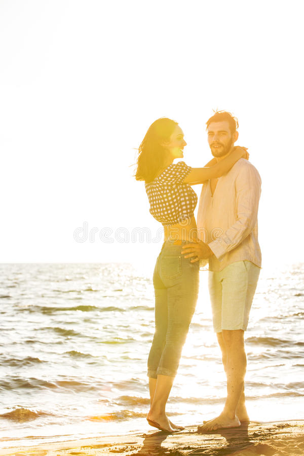 Glück und romantische Szene von Liebespaaren tut sich auf dem Strand zusammen stockbild