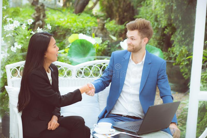 Glückerfolgs-Teilhaber mit zwei Leuten, der Hände im Büro-, Geschäftsmann- und Geschäftsfrauhändedruck erfolgreich rüttelt stockfoto