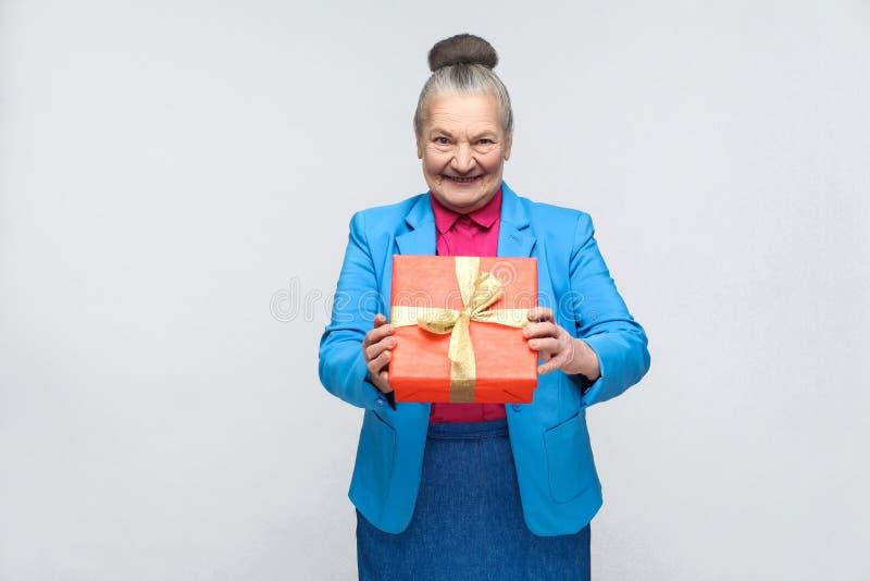 Glückfrau, die rote Geschenkbox und das toothy Lächeln hält stockfoto