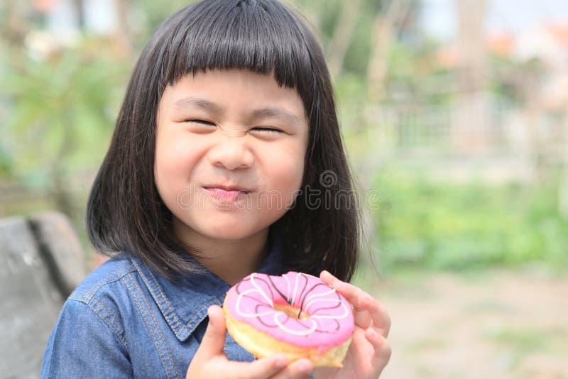 Glückgesicht von asiatischen Kindern mit süßem Donut in der Hand lizenzfreies stockbild