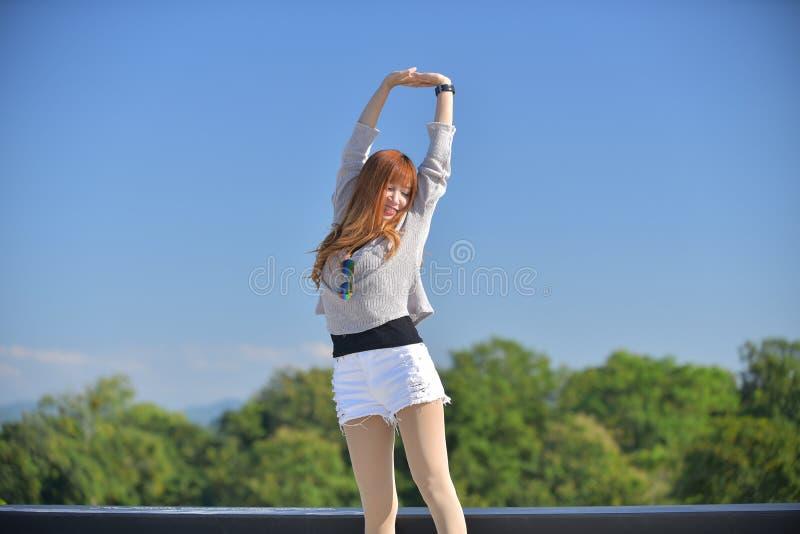 Glücklich entspannen Sie sich lange Haardame Asiens in der legeren Kleidung im Garten lizenzfreies stockbild