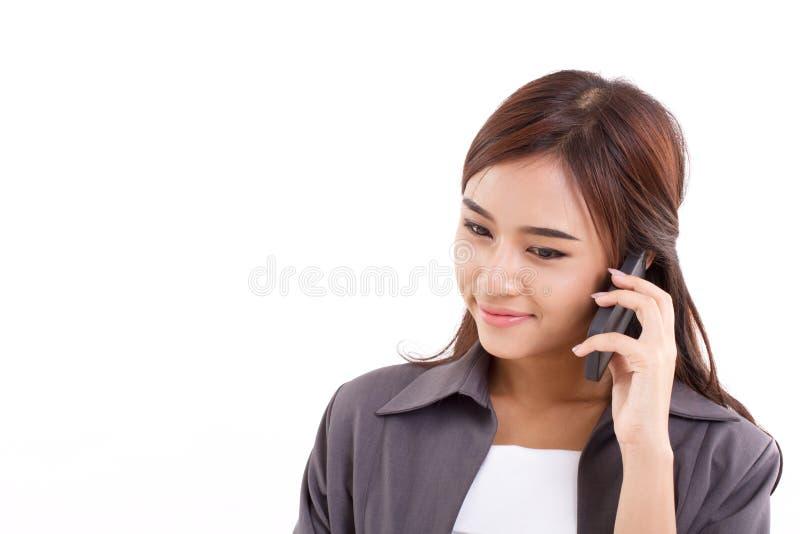 Glücklich, lächelnd, positive Geschäftsfrau, die auf ihr intelligentes Telefon hört stockfotos
