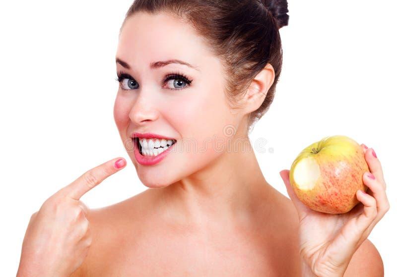 Glücklich lächelnde Frau mit einem reifen Apfel stockfoto