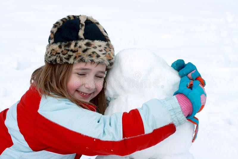 Glücklich mit ihrem Schneemann lizenzfreie stockbilder
