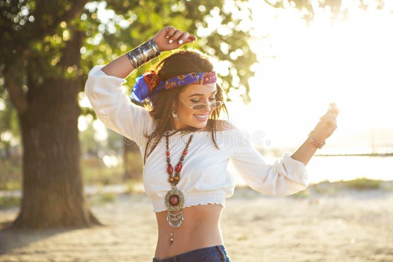 Glücklich nehmen Sie Sonnenbräunefrau in den Jeans ab, die auf den Strand tanzen stockfotografie