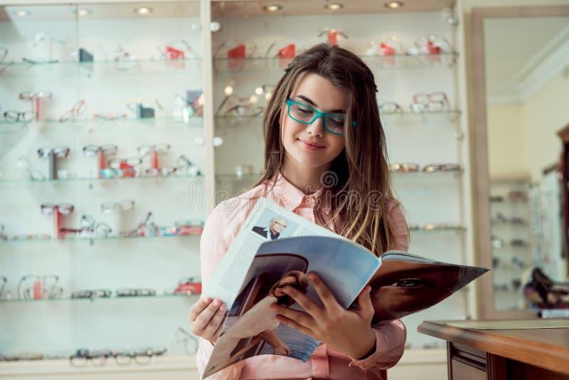 Glücklich, Wörter ohne Unschärfe offenbar zu sehen Innenporträt der erfüllten attraktiven europäischen Frau, die im Optiker sitzt lizenzfreie stockfotografie