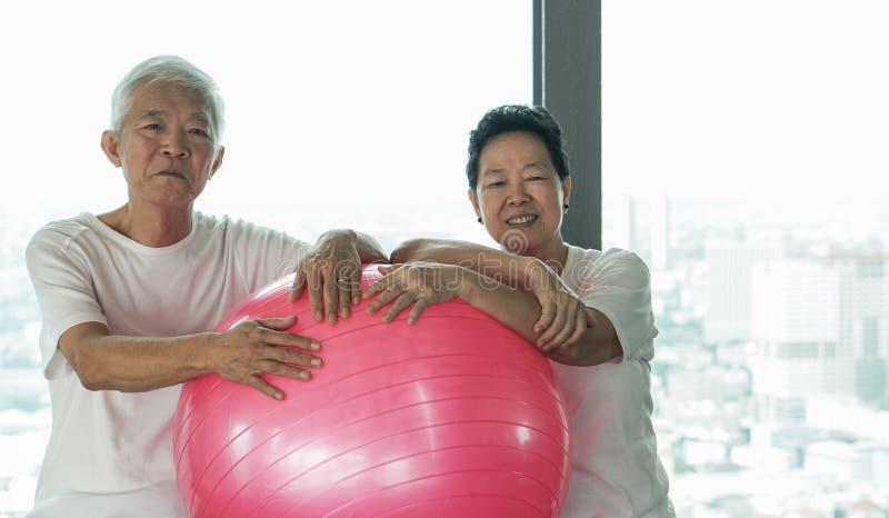 Glückliche ältere asiatische Paare haben Spaß mit Turnhallenyoga-Ballklasse lizenzfreie stockbilder