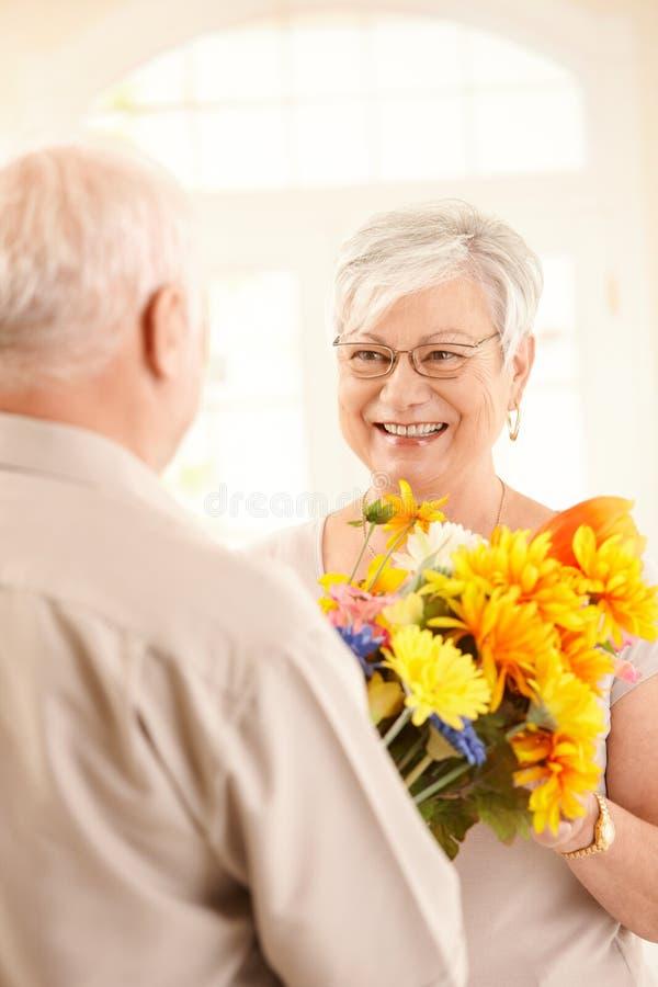 Glückliche ältere Dame, die Blumen empfängt lizenzfreies stockbild