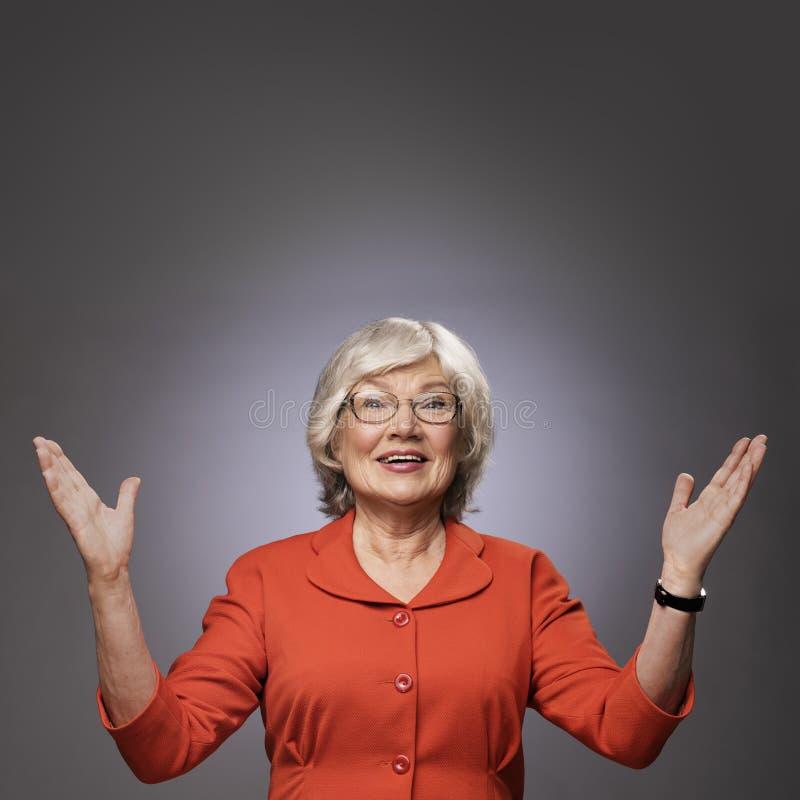 Glückliche ältere Dame mit den Händen oben stockbild
