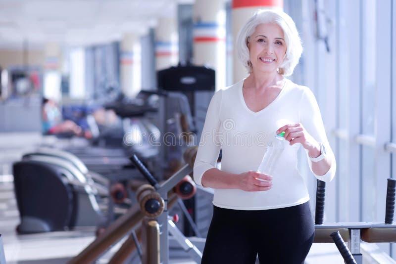 Glückliche ältere Dame mit Flasche an der Turnhalle stockfotografie