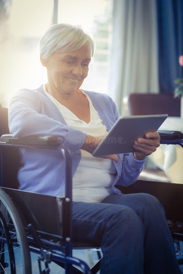 Glückliche ältere Frau auf Rollstuhl unter Verwendung der digitalen Tablette stockbild