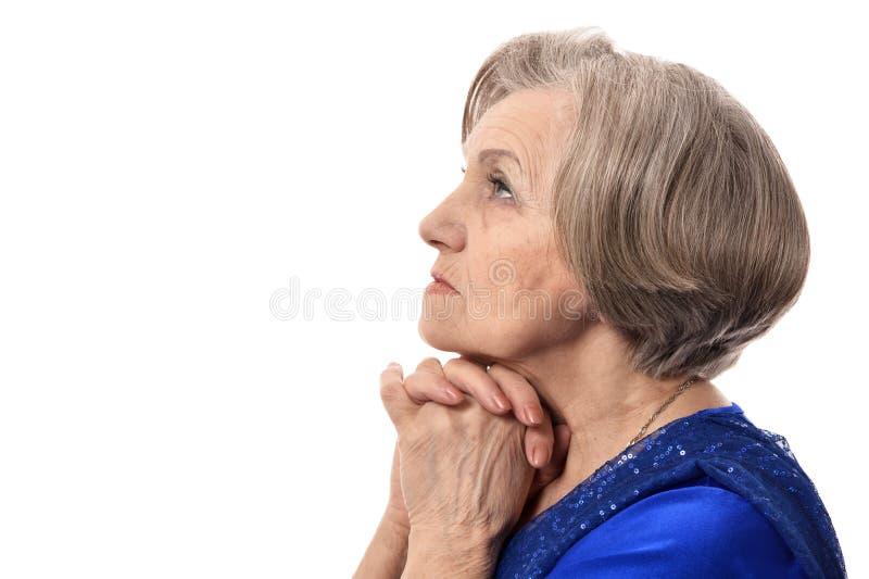 Glückliche ältere Frau beim elegantes Kleiderbeten lokalisiert stockbilder