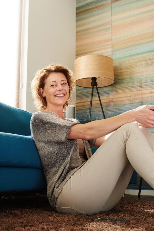 Glückliche ältere Frau, die auf Boden der gemütlichen Wohnung sitzt lizenzfreies stockbild