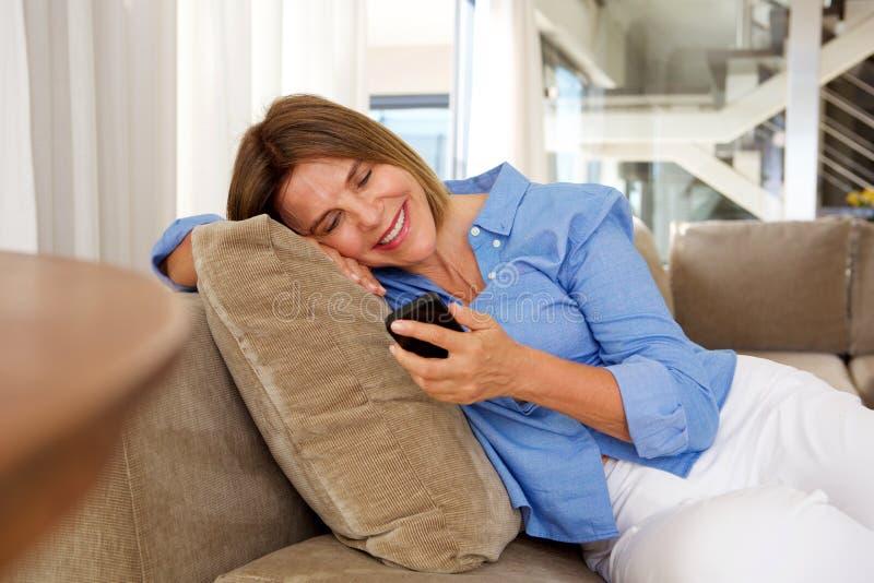 Glückliche ältere Frau, die auf dem Sofa betrachtet Handy sitzt stockbild