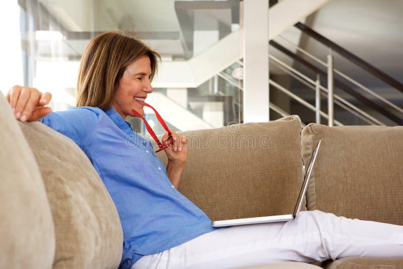 Glückliche ältere Frau, die auf dem Sofa schaut Laptop sitzt stockfotografie