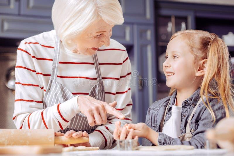 Glückliche ältere Frau, die auf die Plätzchen in den Händen ihrer Enkelin zeigt stockfoto